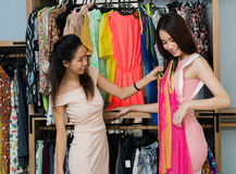 Try on this!. An attractive lady advising her girlfriend to try on the fashionable dress in the mall stock photos