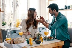 Try this!. Beautiful young couple enjoying healthy breakfast while sitting in the kitchen at home royalty free stock image