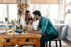 Try it!. Beautiful young couple enjoying healthy breakfast while sitting in the kitchen at home royalty free stock photography