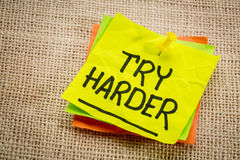 Try harder motivation note. Try harder - motivation words on a yellow sticky note against burlap canvas stock photography