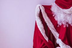 Try on a new image!. The coat, cap and beard of Santa are waiting for the New Year. Become a magician, try on a new image, fulfill the wishes of your loved ones Stock Photography