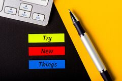 Try New Things colorful memo on workplace background. Motivation is getting better, knowing the world