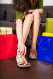Try on shoes at shop. Woman detail sitting on a brown sofa between shopping bags Royalty Free Stock Photo