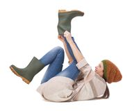 Try This On For Size. Beautiful young woman isolated on white background and putting on gardening boots Stock Photo