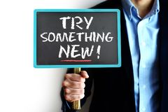 Try something new advice handwritten on small chalkboard held by a businessman. Try something new advice text on small chalkboard held by a businessman Royalty Free Stock Images