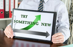 Try something new concept on a clipboard. Try something new concept shown by a businessman Stock Images