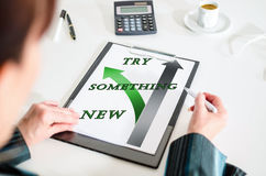Try something new concept on a clipboard. Woman looking at a try something new concept Royalty Free Stock Photography