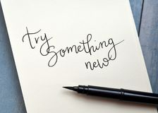 TRY SOMETHING NEW hand-lettered in notepad with brush pen. On retro blue wooden background stock images
