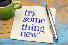 Try something new - text on napkin. Try something new advice or reminder - handwriting on a napkin with a cup of coffee Royalty Free Stock Photos