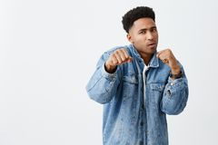 Try to beat me. Close up of young good-looking dark-skinned men with curly hair in white t shirt and denim jacket. Try to beat me. Close up of young good-looking stock image
