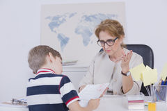 Try to concentrate on the task. Young boy looking at his test result with bad mark stock photo