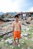 Tryck ned pojken efter jordskalvkatastrof Arkivfoto