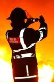 Tryck på tjänstemanbrandmannen med kameran på brand Arkivfoton