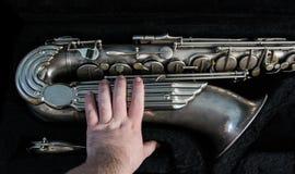 Trycka på en silversaxofon i dess fall arkivbild