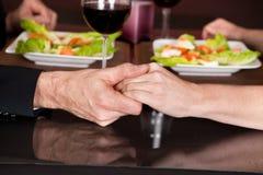 Trycka på händer på den romantiska matställen i restaurang royaltyfria foton