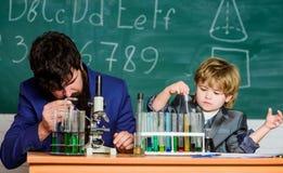 Trycka på livför evigt fader och son på skola lärareman med pysen skolalabbutrustning tillbaka skola till royaltyfri foto