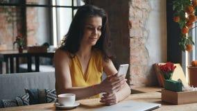 Tryckande på skärm för charmig innehavsmartphone för ung dam som ler i modernt kafé lager videofilmer