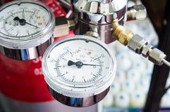 Tryckmätare på en gasregulator av en gasbehållare i ett laboratorium Arkivfoto