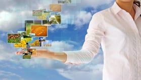 tryckning av multimedia i hand på blå himmel Arkivfoto