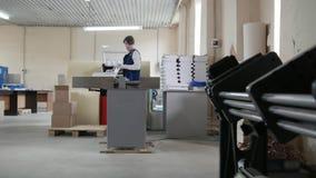 Tryckoperatören sätter ett ark av papper, bred vinkel stock video