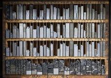Tryckpressbokstavskvarter i en trähylla Royaltyfri Foto
