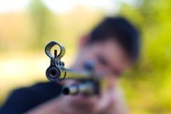 trycksprutaman som pekar geväret Arkivfoto