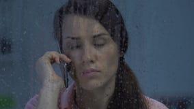 Tryckt ned ensam kvinna som talar på telefonen, dåliga nyheter på den regniga dagen, frustration arkivfilmer