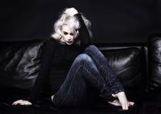 Tryckt ned kvinna på sofaen Arkivfoto