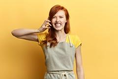 Tryckt ned, olycklig, ilsken frustrerad ung kvinna som talar på telefonen fotografering för bildbyråer