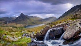 Tryfan i vår med Afonen Lloer i flöde över vattenfallen, Wales royaltyfri bild