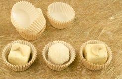 Tryfflar och papper för vit choklad som hemlagade förpackar på guld- bakgrund Royaltyfri Fotografi