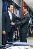 Trying on bespoke suit. Happy Vietnamese men trying on his new bespoke suit in boutique royalty free stock images