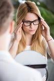 Trying on black rims glasses Stock Image