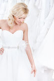 Trying on a charming wedding gown. Young girl is trying on a charming wedding gown, white background royalty free stock photos