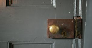 Trying the Door Handle. Close-up of an old fashioned style door knob and lock in a house. The door handle is being tested, twisted and trying to be opened stock footage