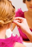 Trying on earrings Royalty Free Stock Photography