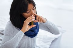 Enthusiastic patient curing terrible flu. Trying hard. Young energetic woman trying hard to cure her flu while using nasal drops Stock Image