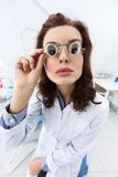 Trying on medical spectacles, serious Royalty Free Stock Photography