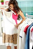 Trying on new dress. Portrait of pretty woman trying on new dress in clothing departmant Stock Images