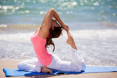 Trying some yoga poses at the beach Stock Photos