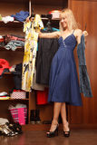 Trying to choose. Beautiful young woman stands near her wardrobe  with two different dresses and trying to choose Royalty Free Stock Photo