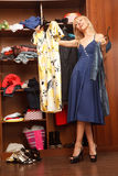 Trying to choose. Beautiful young woman stands near her wardrobe  with two different dresses and trying to choose Stock Photos