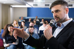 Trying to come up with the simplest explanation. Close-up of a young academic teacher holding a microphone and pointing at something during college classes royalty free stock photos