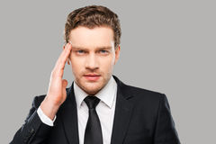 Trying to concentrate. Frustrated young man in formalwear touching head with hand and looking at camera while standing against grey background Royalty Free Stock Images