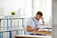 Trying to concentrate. Tired businessman sitting by workplace in office Royalty Free Stock Photography