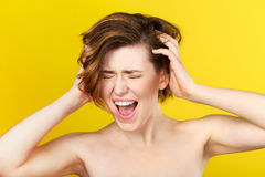 Trying to cope with own feelings. Emotional moment. Close up shot of pretty young woman holding her head with hands and screaming loudly Stock Photos