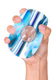 Trying to destroy your data. A close up of a hand squeezing a CD or DVD, shoot against very bright white screen royalty free stock images