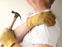 Trying to do home maintenance with shoulder pain. A man grips his shoulder as he tries to do repairs royalty free stock photography