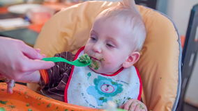 Trying to feed a baby. Small cut child seating in his chair dirty around his face and mother is trying to feed him with a spoon full of food stock video