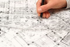 Trying to find the solution. Architect searching for construction solution over a very messy blueprint full of ideas Stock Images